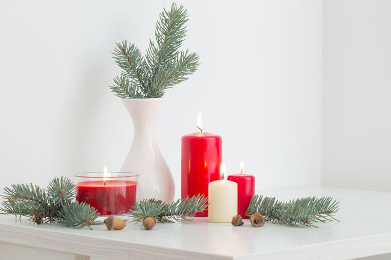 Rami di pino in un vaso bianco e candele rosse, ideale per decorare a Natale.