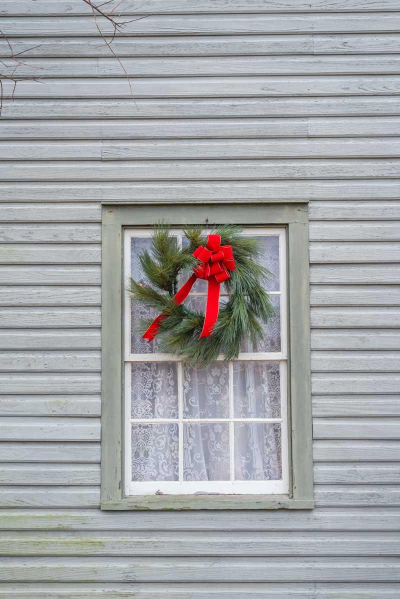 Finestra decorata con una corona natalizia.