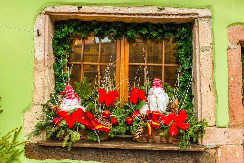 Decori di natale per finestra, festone, piccoli babbi natale, rami di pino.