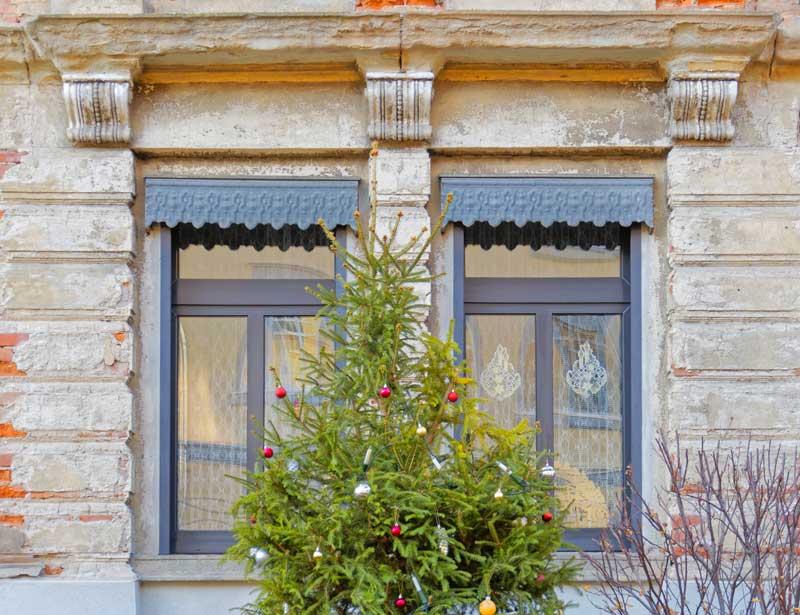 Albero di Natale fuori al giardino in mezzo a due finestre.
