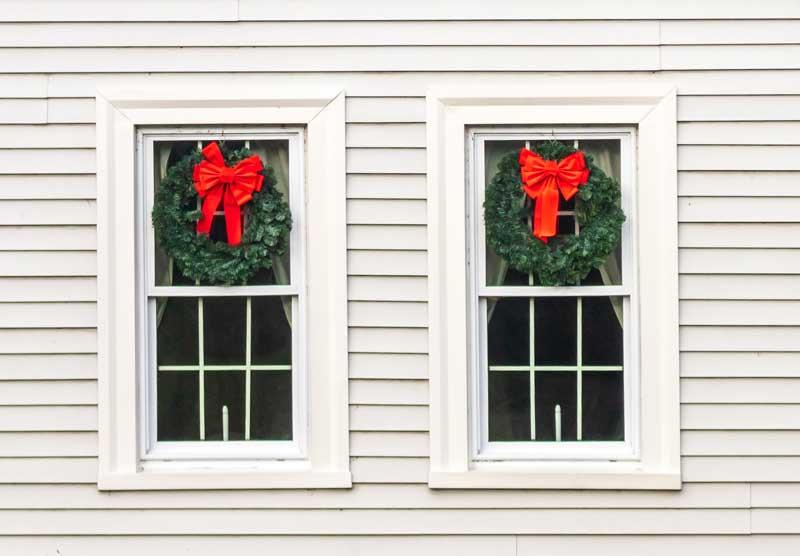 Decorazioni natalizie fai da te per queste finestre con due corone con fiocco rosso.