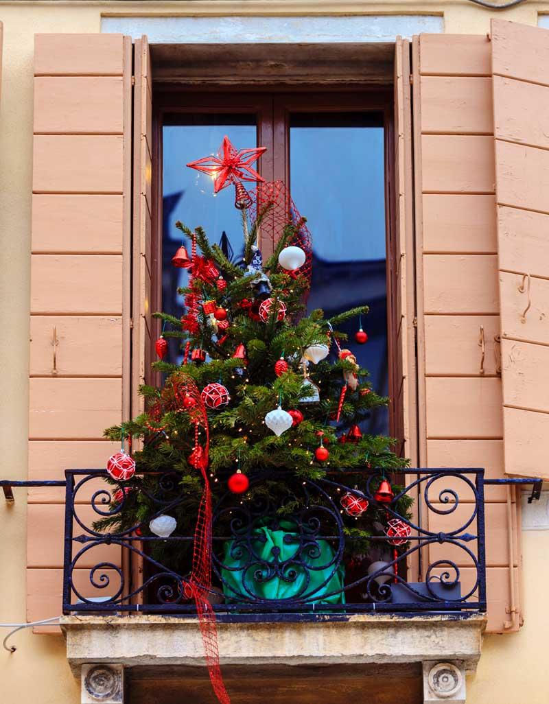 Piccolo balcone con albero di Natale addobbato di rosso.