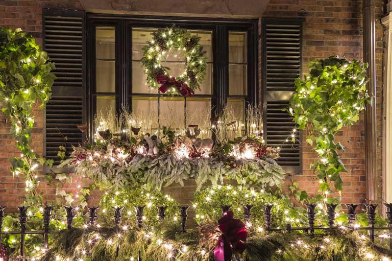 Bellissimo addobbo natalizio esterno con lucette e composizioni di rami di pino e ghirlande.