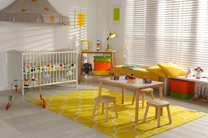 Cameretta per neonato bianca con grande tappeto giallo.