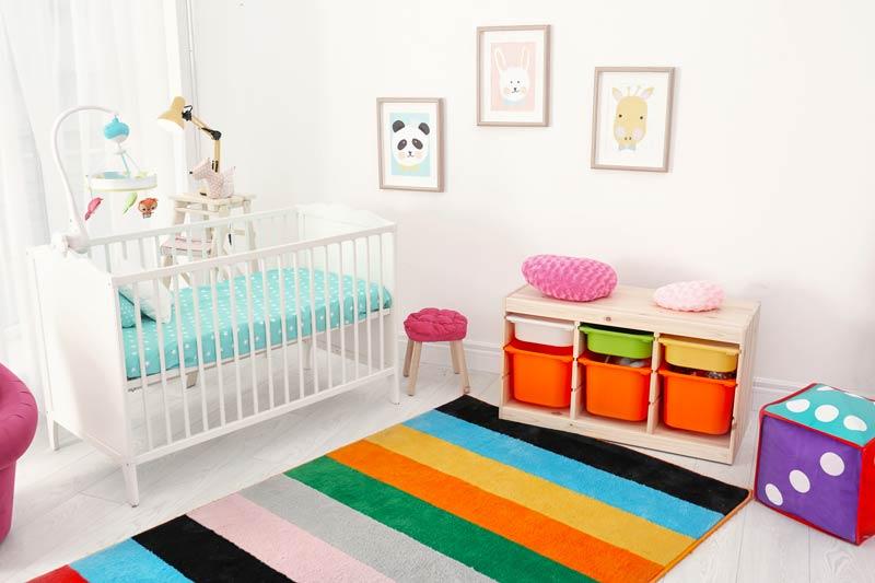 Cameretta per neonato con pareti bianche e tappeto colorato.