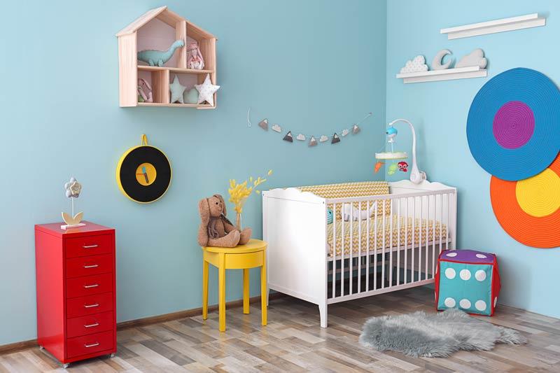 Bellissima camera per neonato color celeste, culla bianca e decorazioni colorate.