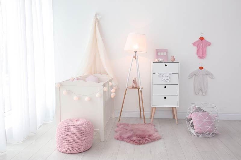 Cameretta per neonata bianca e rosa con pouf davanti alla culla.