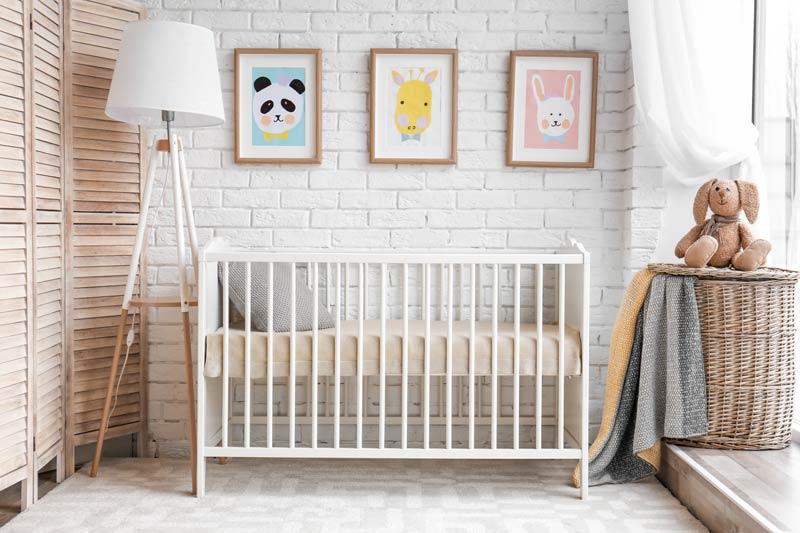 Cameretta per neonata con lampadario e separè in legno, parete con mattoni a vista bianchi, ideale per uno stile vintage.