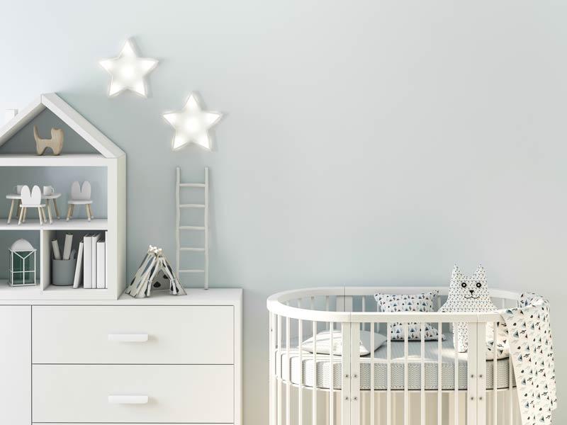 Cameretta per neonato con parete celestino e mobili bianchi, belle stelle luminose sulla parete.