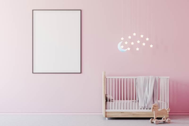 Stanzetta per neonata con parete rosa e culla bianca, bellissimo lampadario con stelline luminose.