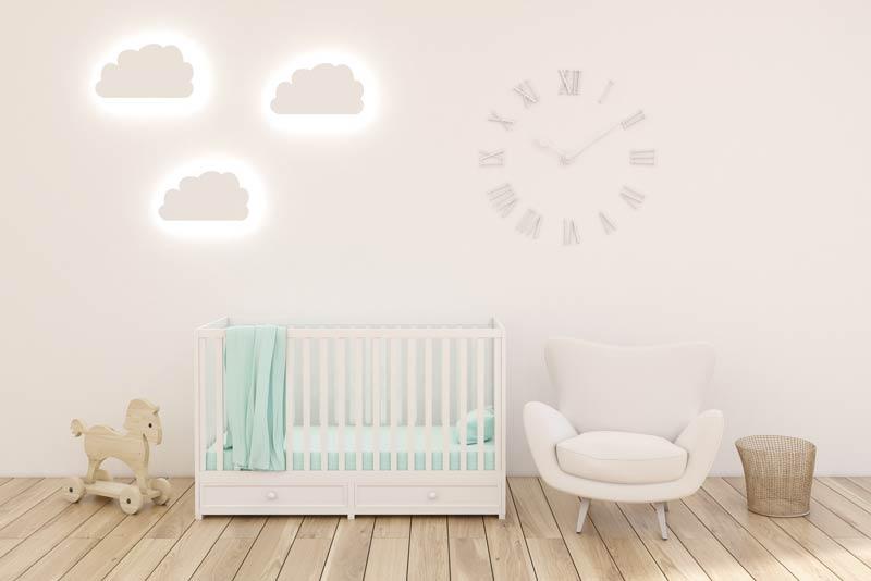 Cameretta per neonati con pareti decorate con delle nuvole illuminati.