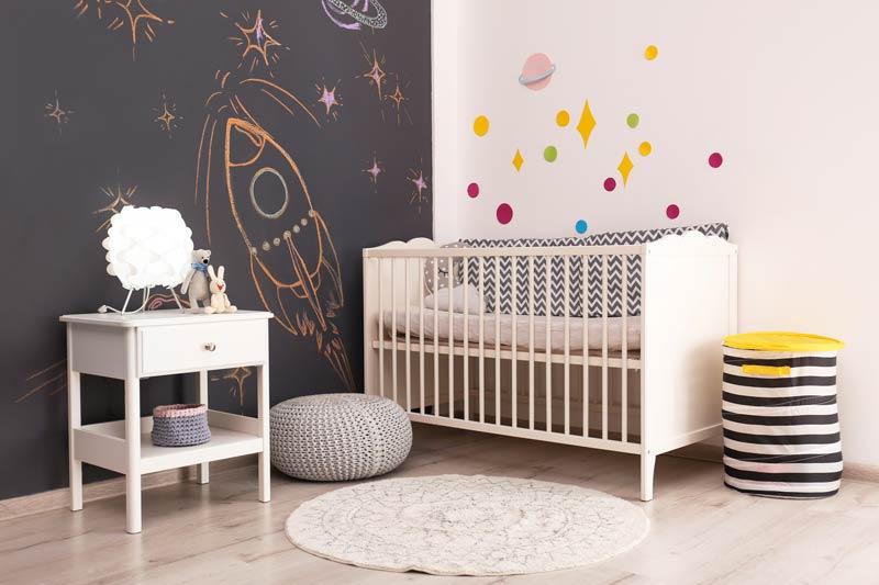 Camera per bimbo con una parete bianca e un altra con pittura lavagna, ideale per far disegnare il bambino.