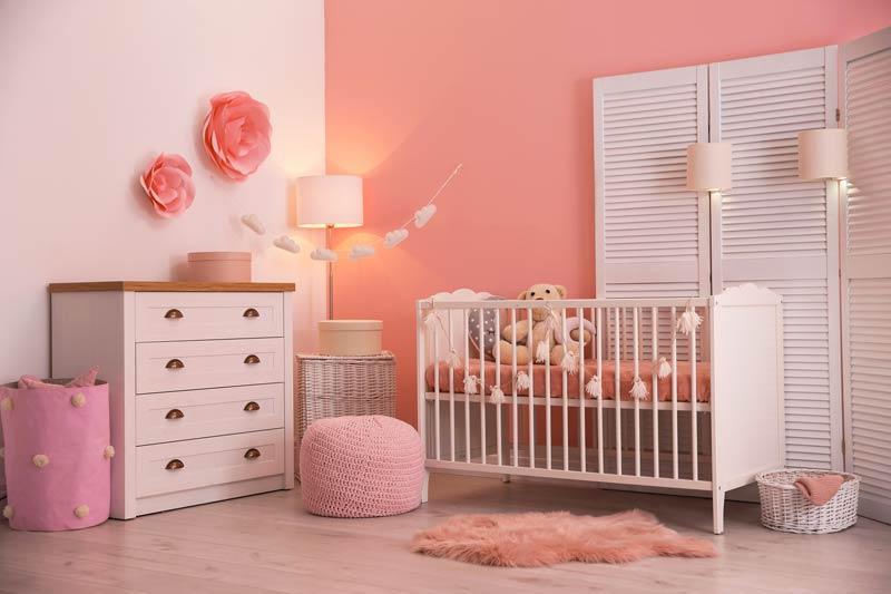 Camera per neonata con pareti rose e bianche, bello il separè in legno bianco.