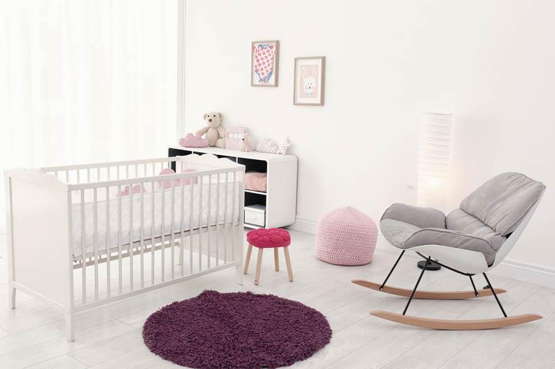 Bella cameretta per femminuccia bianca e rosa con sedia a dondolo.