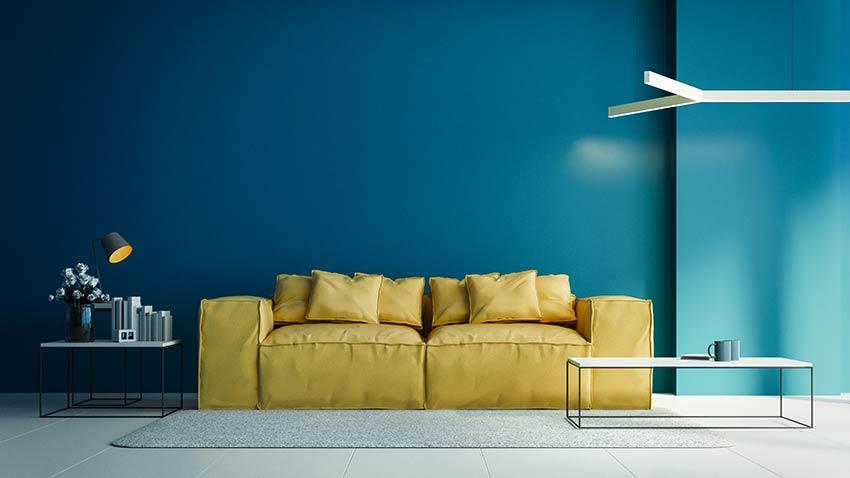 Soggiorno con divano giallo e parete color Bleached Coral il pantone 2020.