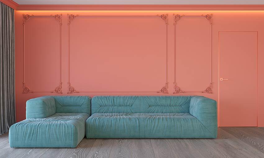 Salotto con parete color pantone 2019 e divano color blu pantone 2020.
