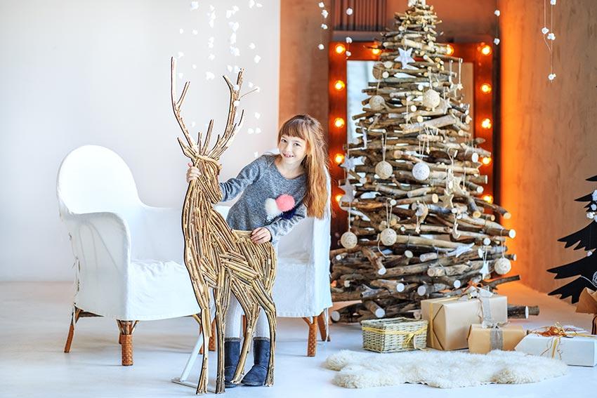Renne di Babbo Natale stilizzata realizzata in legno con albero realizzato con tronchi di legno.