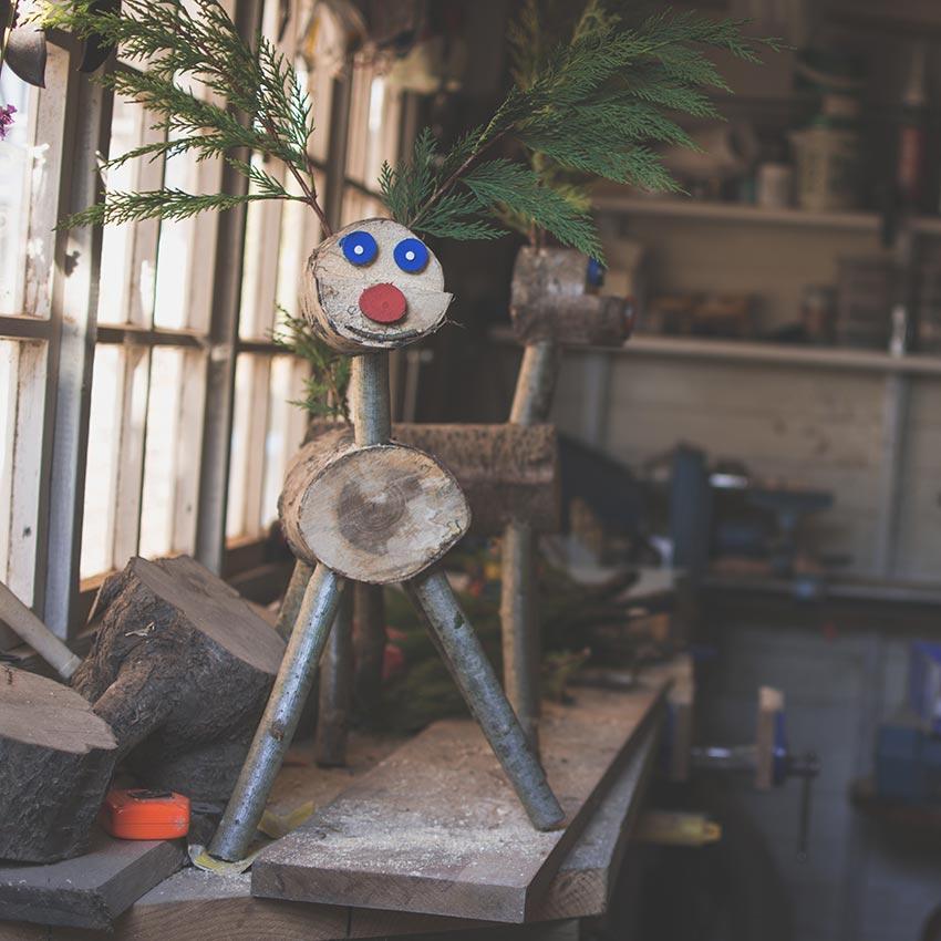 Renne di Babbo Natale fai da te con tronchi e rami di pino.