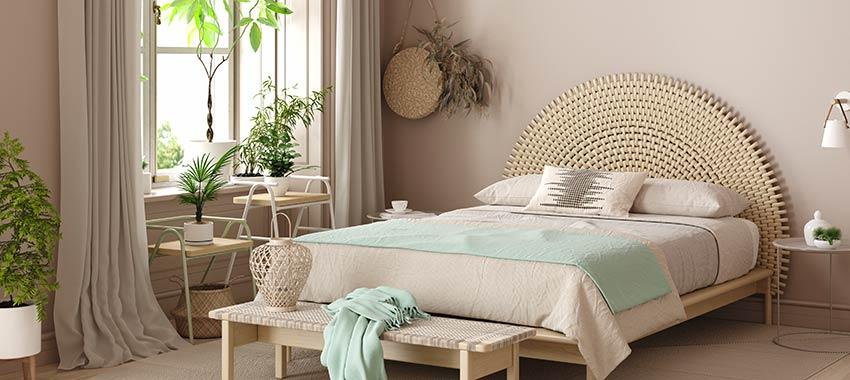 Bellissima camera da letto con tende e pareti color tortora, testata letto originale e coperta verde acqua.