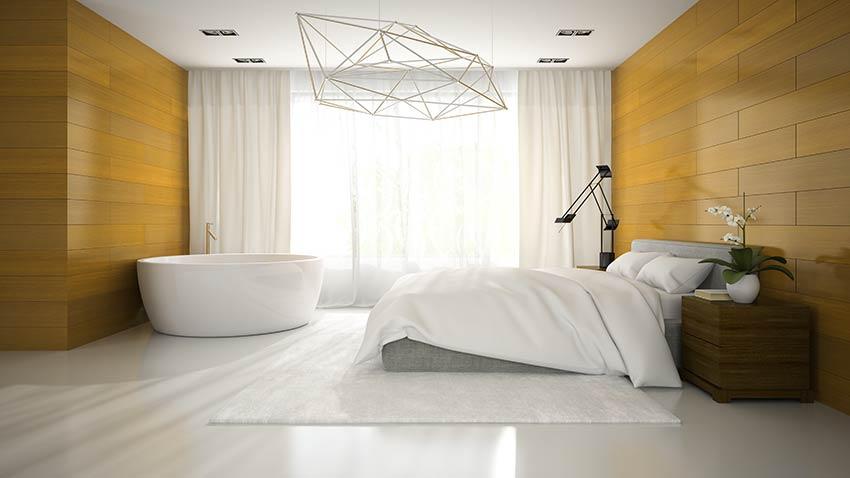 Grande camera da letto con vasca, rivestimento murale in legno e grande tende bianche.