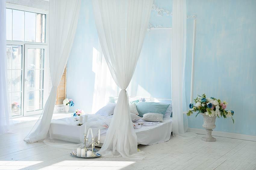 Grande tende bianche attorno ad un letto matrimoniale.