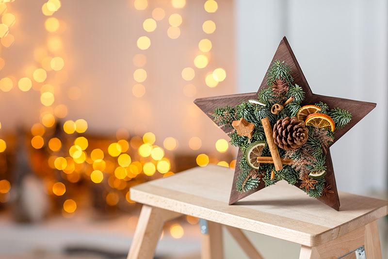 Stella in legno con decorazioni con rami di pino.
