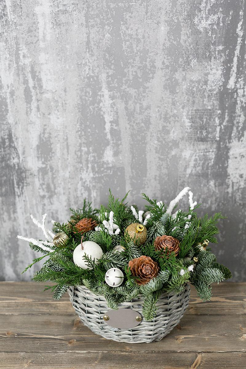 Vaso in vimini con pigne, palline natalizie e rami di pino.