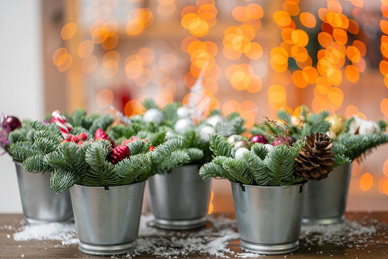 Vasetti decorati con rami di pino, pigne e palline di natale.