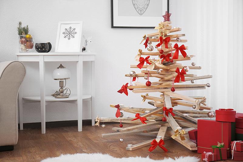 Albero di Natale realizzato con pallet di legno riciclato decorato con fiocchetti rossi.