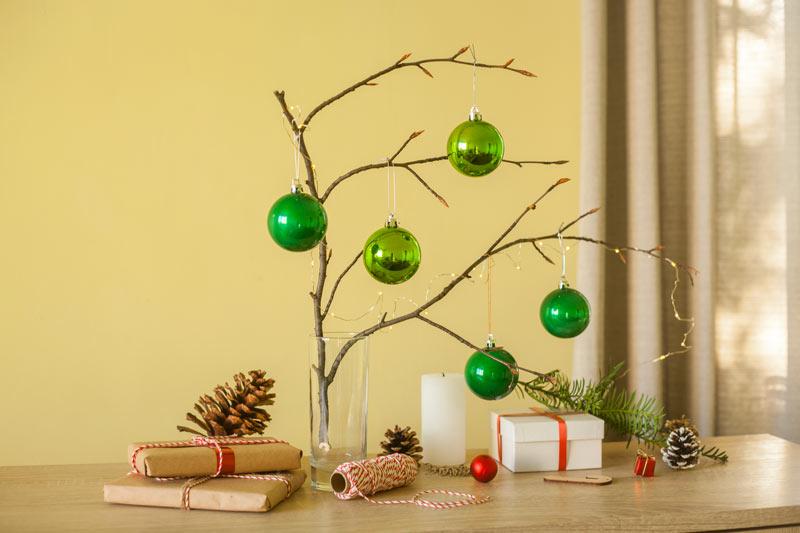 Addobbi natalizi in legno, ramo in un vaso con palline di Natale verde.