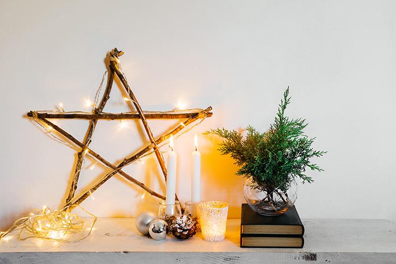 Stella di Natale realizzata in legno con rami e catena luminosa.