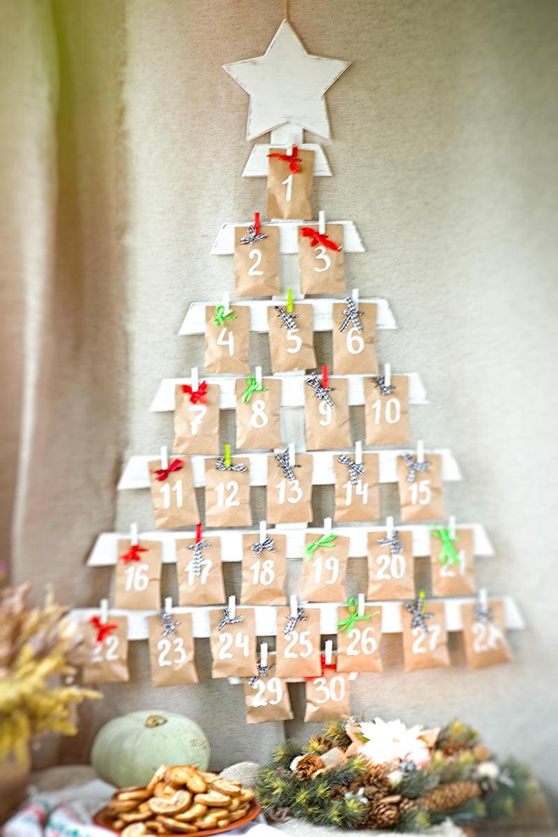 Un calendario di Natale di legno a forma di albero.
