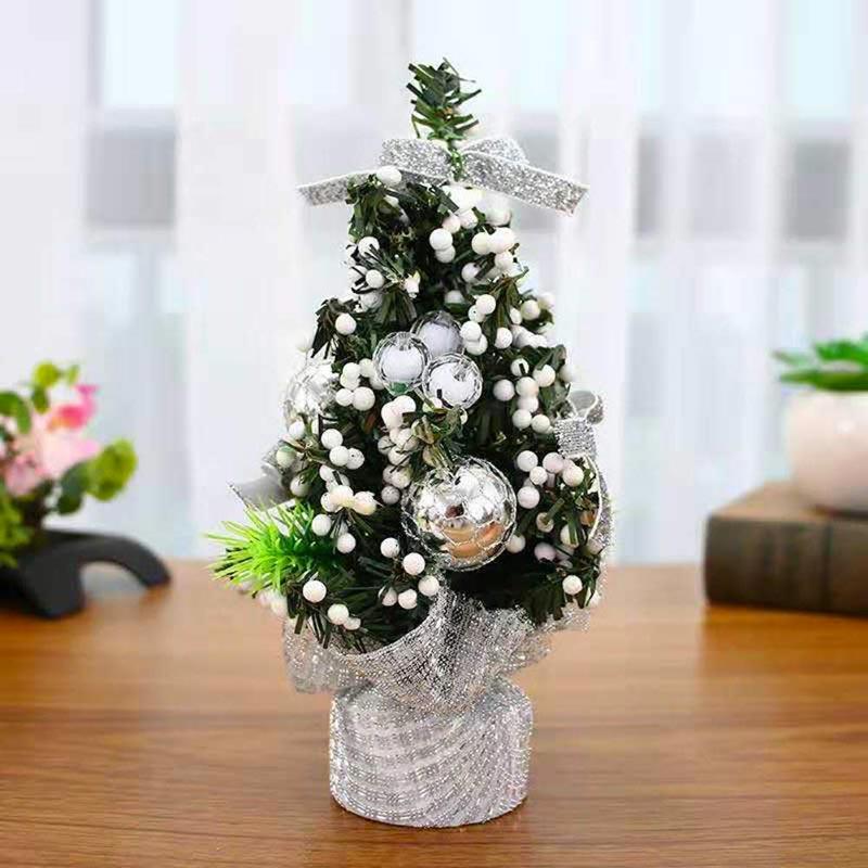 Piccolo albero di natale artificiale verde con decorazioni bianche e palline dorate. Fiocco e base con nastro argentato.