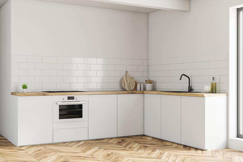 Piccola cucina ad angolo bianca con top in legno chiaro.