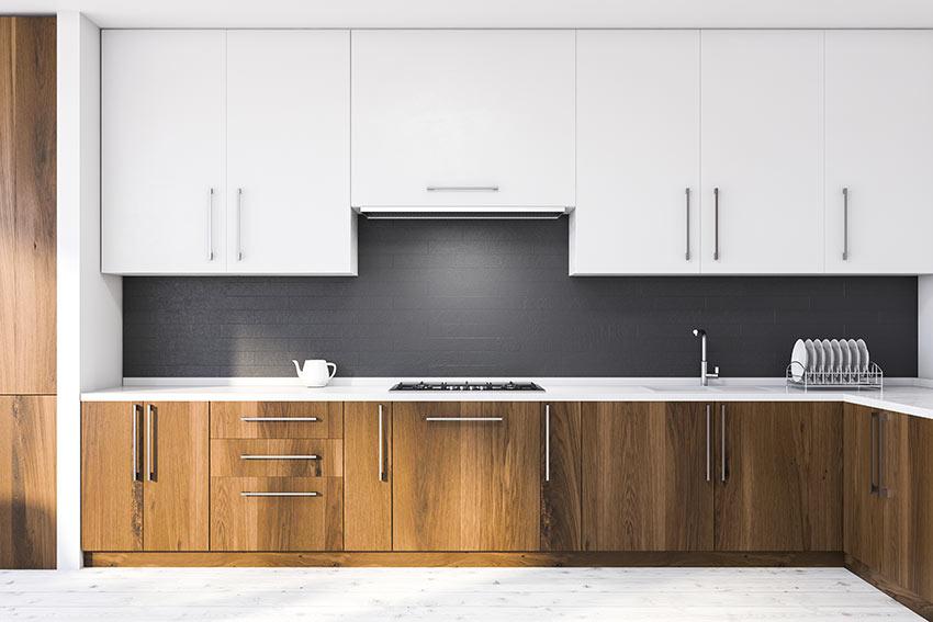 Cucina ad angolo bianca e legno con para schizzi neri effetto mattoni.