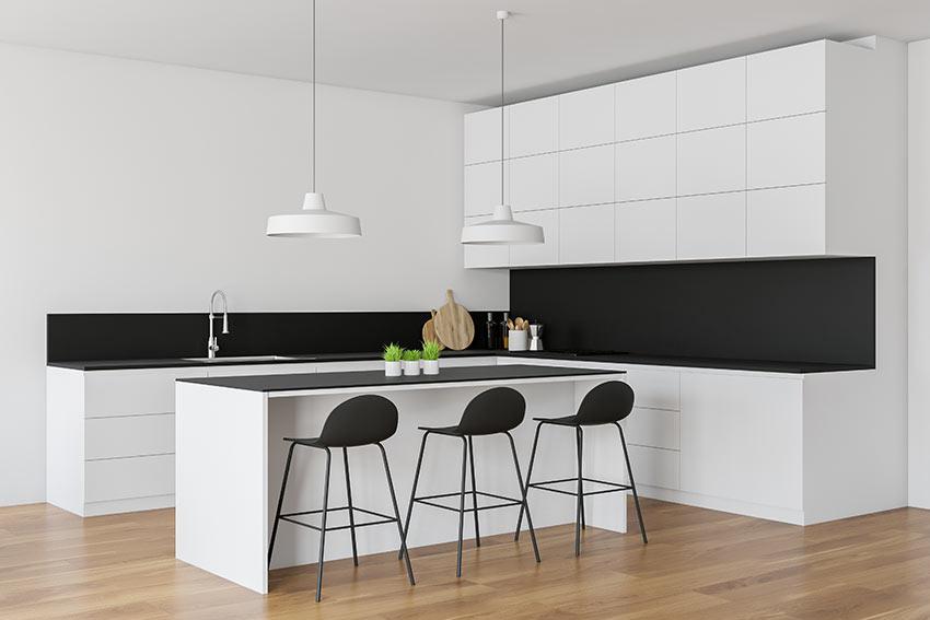Cucina moderna di design bianca e nera ad angolo con isola centrale.