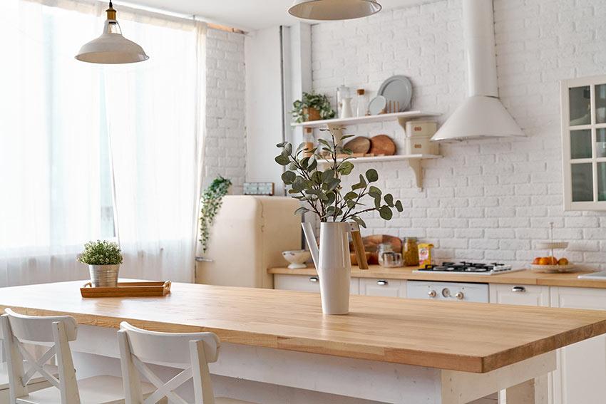 Una bella cucina bianca e legno dallo stile country, splendida la parete in mattoni a vista bianchi.