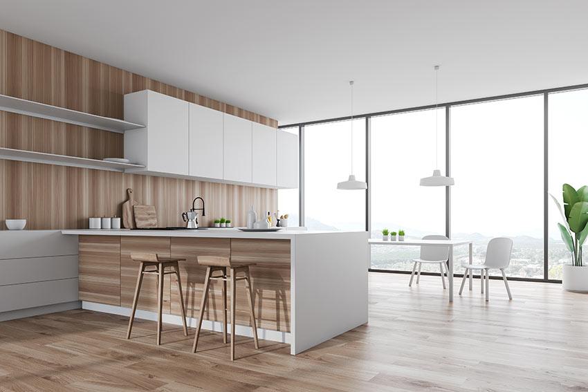 Cucina moderna bianca con penisola e pannelli in legno.