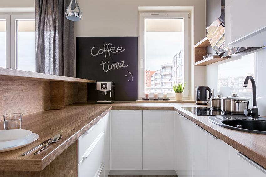 Piccola cucina moderna stretta e lunga bianca con top in legno.