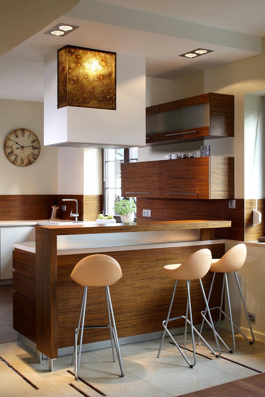 Una cucina in legno scuro con penisola e cappa super moderna.