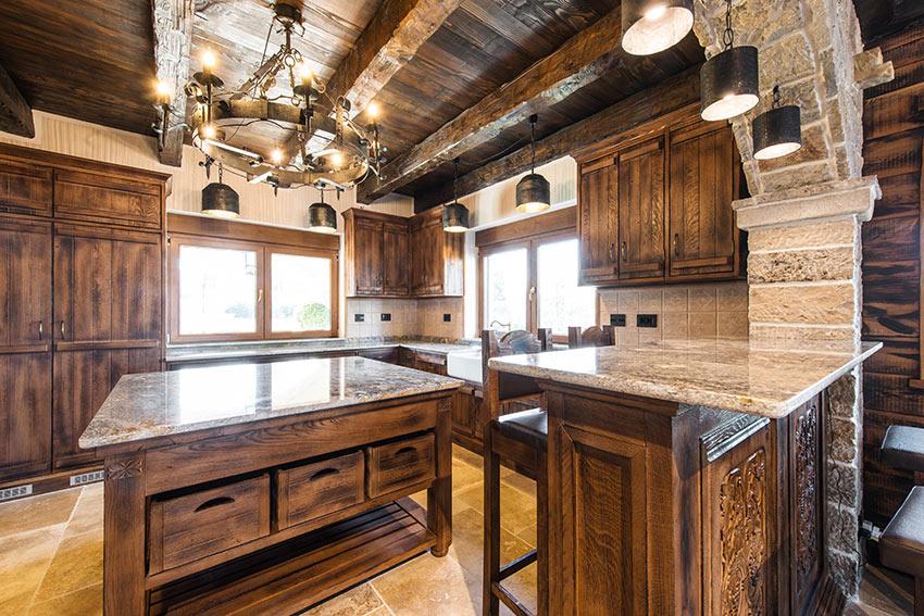 Una cucina in legno scuro stile rustico, travi in legno e pareti in pietra naturale.