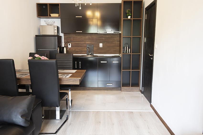 Piccola cucina moderna in legno con sportelli neri.