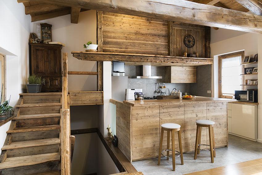 Bellissima cucina in legno grezzo con isola centrale e sgabelli.
