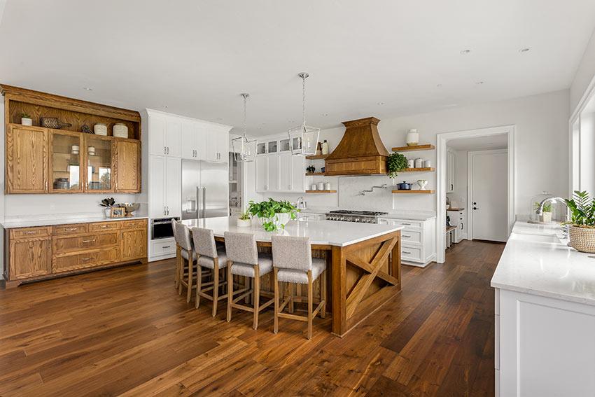 Una cucina tra rustica e moderna, bianca e legno naturale con isola centrale.