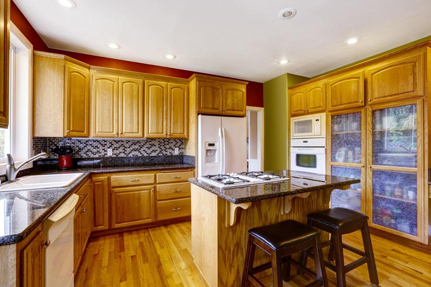 Cucina in legno di pino chiaro angolare con piccola isola centrale.