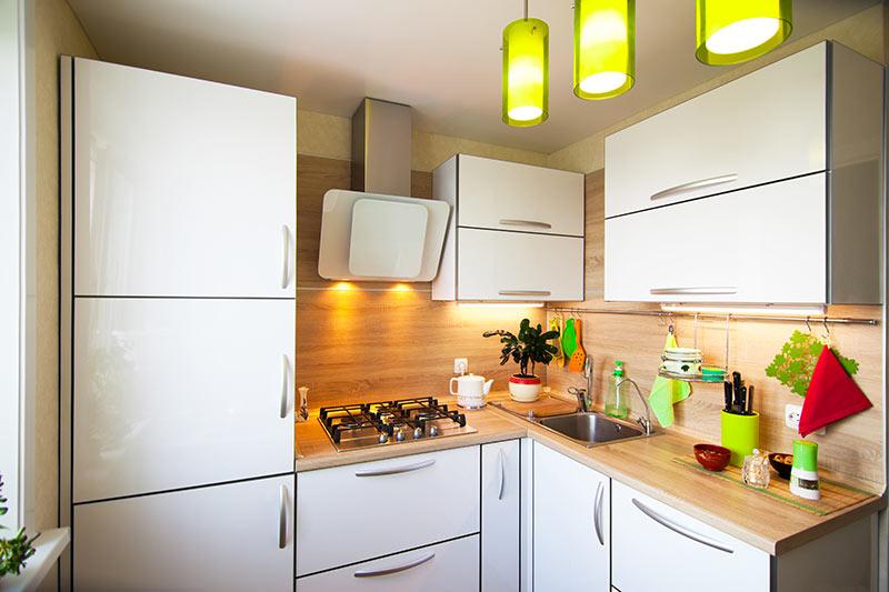 Cucina piccola con lampadari gialli sospesi.