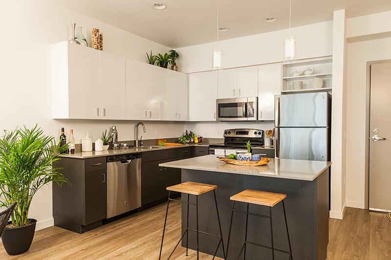 Cucina moderna piccola ad angolo con mobili neri, pensili bianchi e top in marmo.