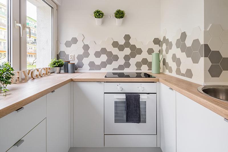 Cucina ad U bianca con top in legno, ideale per piccoli spazi.