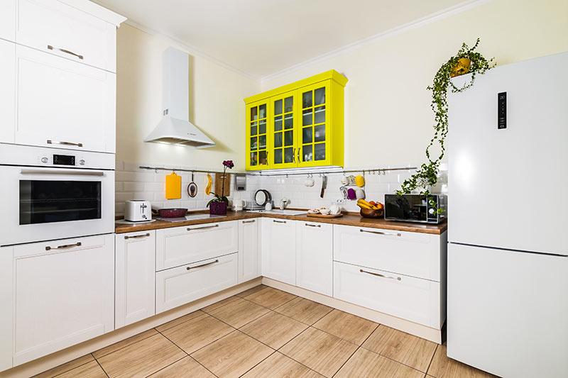 Piccola cucina ad angolo bianca con un pensile giallo, ideale in una casa stile moderno.