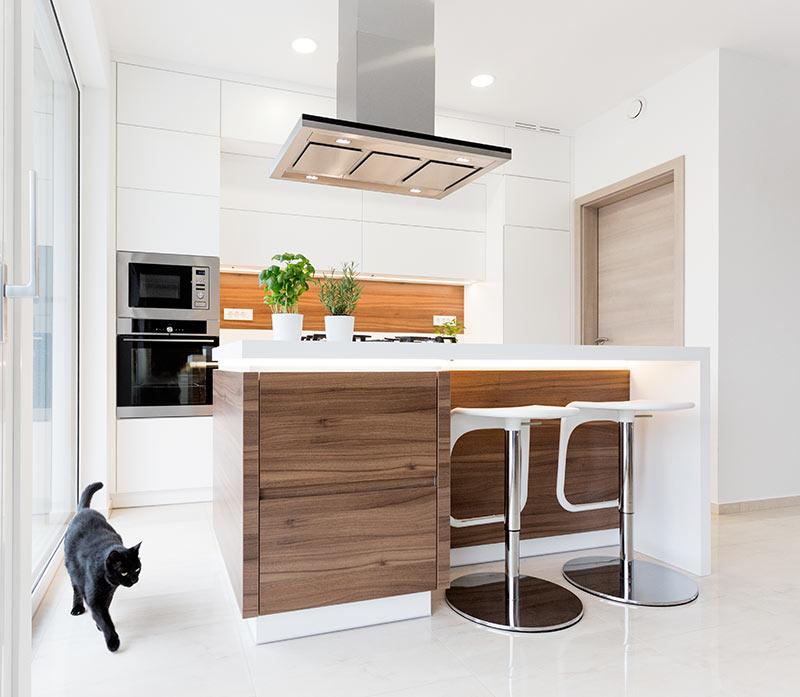 Piccola cucina moderna con isola centrale bianca e legno.